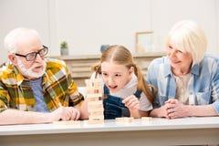 Morföräldrar med sondottern som spelar jengaleken tillsammans hemma royaltyfria bilder