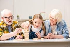 Morföräldrar med sondottern som spelar jengaleken tillsammans hemma arkivbild