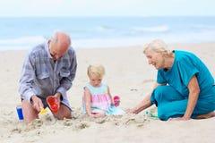 Morföräldrar med sondottern som spelar på stranden Arkivbilder