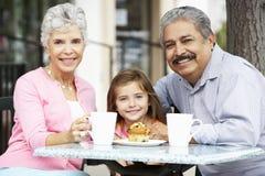 Morföräldrar med sondottern som tycker om mellanmålet på utomhus- CafÅ ½ Arkivfoton