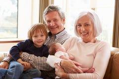 Morföräldrar med sonsonen och nyfött behandla som ett barn sondottern royaltyfri foto
