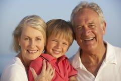 Morföräldrar med sonsonen som tycker om strandferie Arkivbild