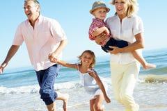 Morföräldrar och barnbarn på strand Royaltyfri Foto