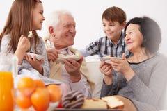 Morföräldrar och barnbarn som äter en kaka arkivbilder