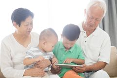 Morföräldrar och barnbarn som använder minnestavlaPC Arkivbild