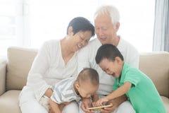Morföräldrar och barnbarn som använder smarta telefoner Arkivfoto