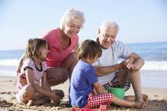 Morföräldrar och barnbarn som bygger sandslotten på stranden royaltyfri fotografi
