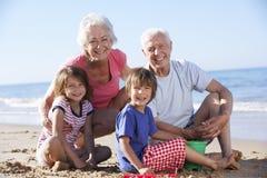 Morföräldrar och barnbarn som bygger sandslotten på stranden arkivbild