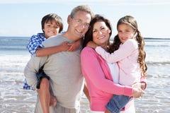 Morföräldrar och barnbarn som har gyckel på strandferie Royaltyfri Bild