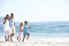 Morföräldrar och barnbarn som promenerar stranden Arkivbild