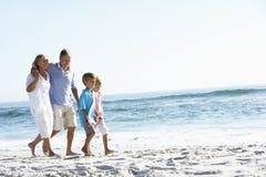 Morföräldrar och barnbarn som promenerar stranden Arkivfoton