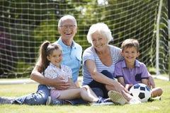 Morföräldrar och barnbarn som spelar fotboll i trädgård arkivbild
