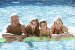 Morföräldrar och barnbarn som tillsammans kopplar av i simbassäng royaltyfri bild