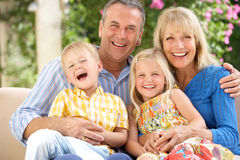 Morföräldrar och barnbarn som tillsammans sitter fotografering för bildbyråer