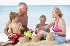 Morföräldrar och barnbarn som tycker om strandferie Arkivfoto