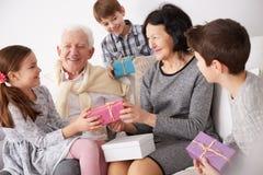 Morföräldrar och barnbarn som utbyter gåvor arkivbild