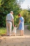 Morföräldrar och behandla som ett barn barnbarnet som utomhus går arkivbild