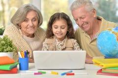 Morföräldrar och liten flicka som använder bärbara datorn Arkivbild