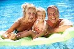 Morföräldrar och sonson i simbassäng Arkivfoton