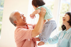 Morföräldrar och sonson som spelar leken inomhus tillsammans Royaltyfri Foto