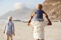 Morföräldrar som bär sonsonen på skuldror promenerar på, stranden royaltyfri foto