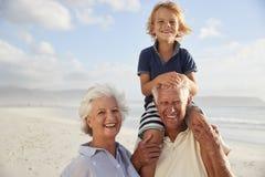 Morföräldrar som bär sonsonen på skuldror promenerar på, stranden royaltyfria bilder