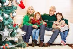 Morföräldrar som firar jul med barnbarn Royaltyfri Fotografi