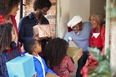 Morföräldrar som hälsar familjen, som de ankommer för besök på juldagen med gåvor arkivfoto