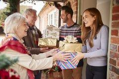 Morföräldrar som hälsas av familjen, som de ankommer för besök på juldagen med gåvor royaltyfri foto