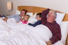 Morföräldrar som håller ögonen på TV i sängen med deras storslagna ungar Arkivfoto