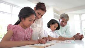 Morföräldrar som hjälper barnbarn med läxa arkivfilmer