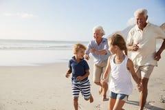 Morföräldrar som kör längs stranden med barnbarn på sommarsemester royaltyfri fotografi