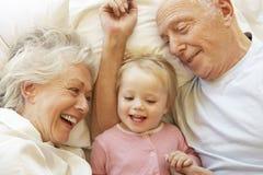 Morföräldrar som kelar sondottern i säng royaltyfri bild