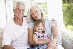 Morföräldrar som kopplar av på Seat med sondottern Royaltyfri Fotografi