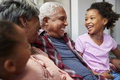 Morföräldrar som kopplar av på Sofa At Home With Granddaughters arkivfoto