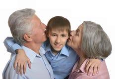 Morföräldrar som kysser sonsonen Royaltyfria Bilder