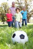 Morföräldrar som leker fotboll med barnbarn Arkivbild