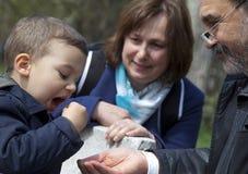 Morföräldrar som matar barnet, parkerar Royaltyfria Foton