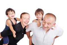 Morföräldrar som piggybacking två pojkar royaltyfria foton