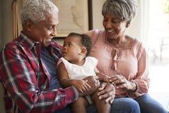 Morföräldrar som sitter på det Sofa With Baby Granddaughter At hemmet arkivfoton