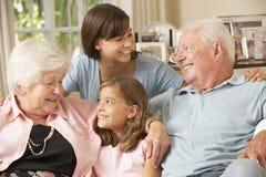 Morföräldrar som sitter på Sofa With Grandchildren Indoors Arkivbild