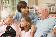 Morföräldrar som sitter på Sofa With Grandchildren Indoors Arkivfoton