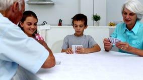 Morföräldrar som spelar kort med deras barnbarn lager videofilmer