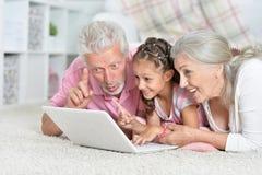 Morf?r?ldrar med hennes sondotter som hemma anv?nder b?rbara datorn arkivbilder