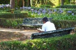 Morfadern läser en bok i parkera, Barcelona arkivbilder