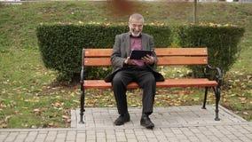 Morfarbruk ett minnestavlasammanträde i parkera på bänken stock video