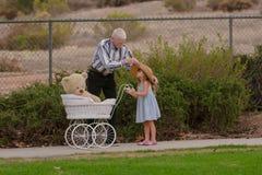 Morfarportionlilla flickan med hatten går på med leksakbarnvagnen Royaltyfri Bild