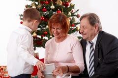 Morföräldrar med sonsonen på jul Royaltyfri Foto