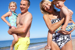 Morföräldrar och barnbarn på strand Arkivfoton