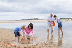 Morföräldrar och barnbarn som spelar på stranden Royaltyfri Bild